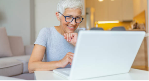 Elderly woman wearing navy-framed glasses smiling looking at healthcare offerings on her white laptop