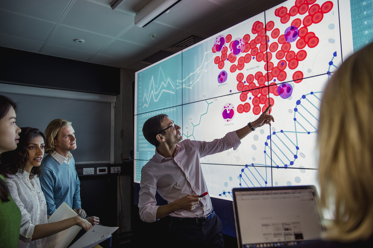 Virtual Clinical Trials digital data presentation on a large smart screen with group of pharma and medical professional analyzing the outcomes of clinical trials