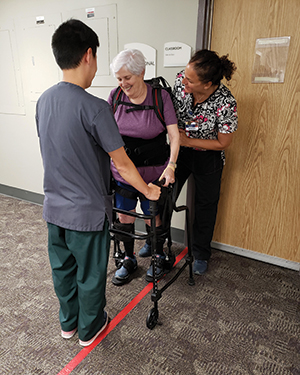 Patient Carol Hanna is assisted on the exoskeleton by physical therapy assistant Jennifer Cowan and rehab technician Brandon Hokama.
