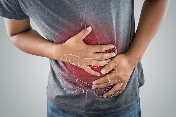 Man holding stomach in pain due to acid reflux and GERD