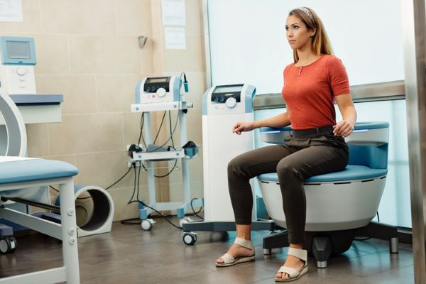 Young woman having non-invasive treatment for urinary incontinence at the clinic