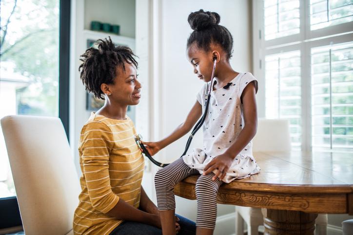 Daughter using stethoscope on mom