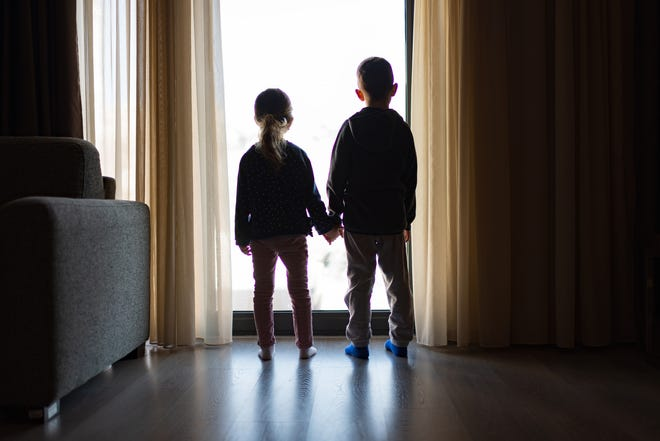 Two kids looking out the window