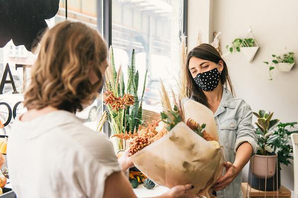 Two women masked in a flower shop