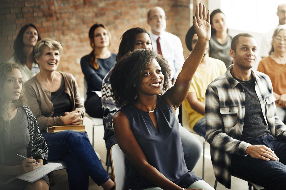 Shutterstock_436596355 Business Team Meeting Seminar Training Concept Woman Raising Hand