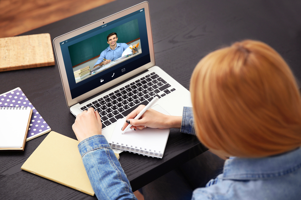 Shutterstock_ 517415605 Woman video conferencing with tutor on laptop at home. Distance education concept.