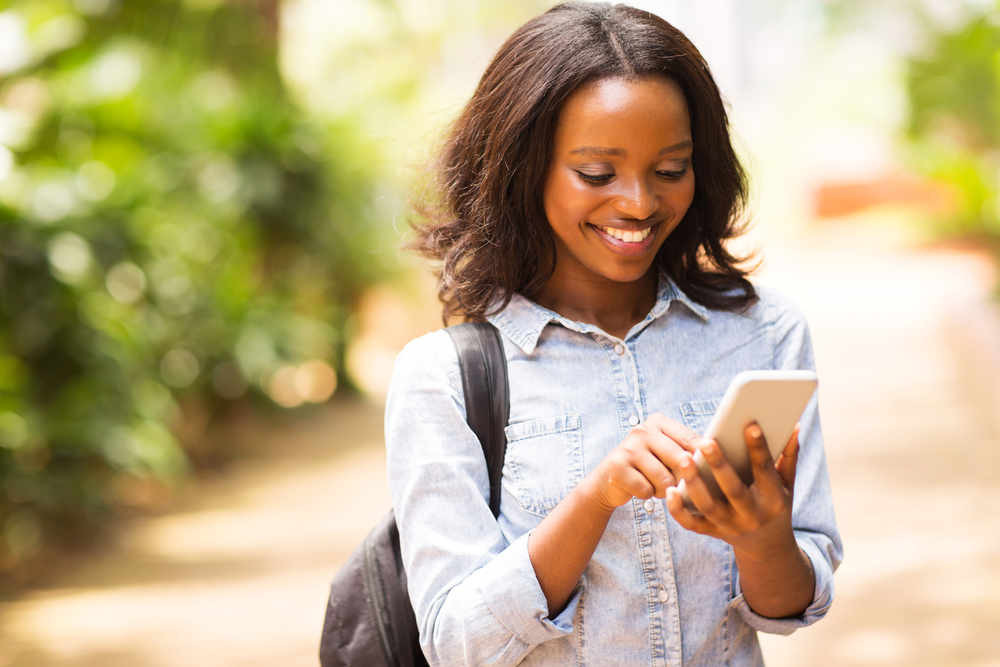 Shutterstock_ 248728171 happy young African American uni student using cell phone