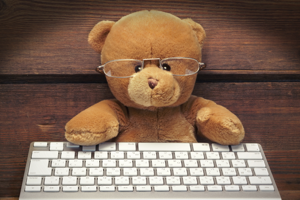 Cute Teddy Bear With A Wireless Keyboard In Front Of An Imaginary Computer Screen At Wooden Wall In Lanters Light. Internet Surfing Or Computer Work Concept
