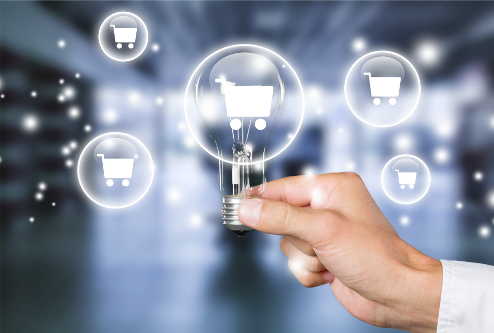 A man's hand holding a light bulb on blurred background with a shopping illustration