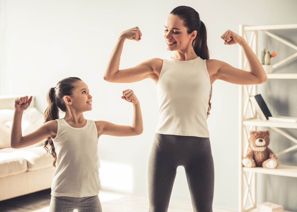 604202222 Beautiful young woman and charming little daughter are showing their biceps and smiling while working out at home