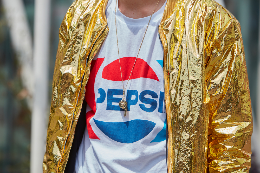 Shutterstock_442337635 Man poses for photographers with shiny golden jacket and Pepsi shirt before Jil Sander fashion show, Milan Men's Fashion Week street style on June 18, 2016 in Milan.