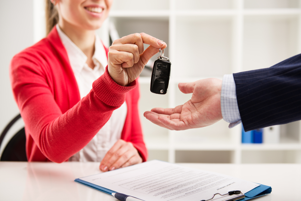 Shutterstock_275655776 Female car agent giving key to male customer for test drive. Partnership and contract signing.