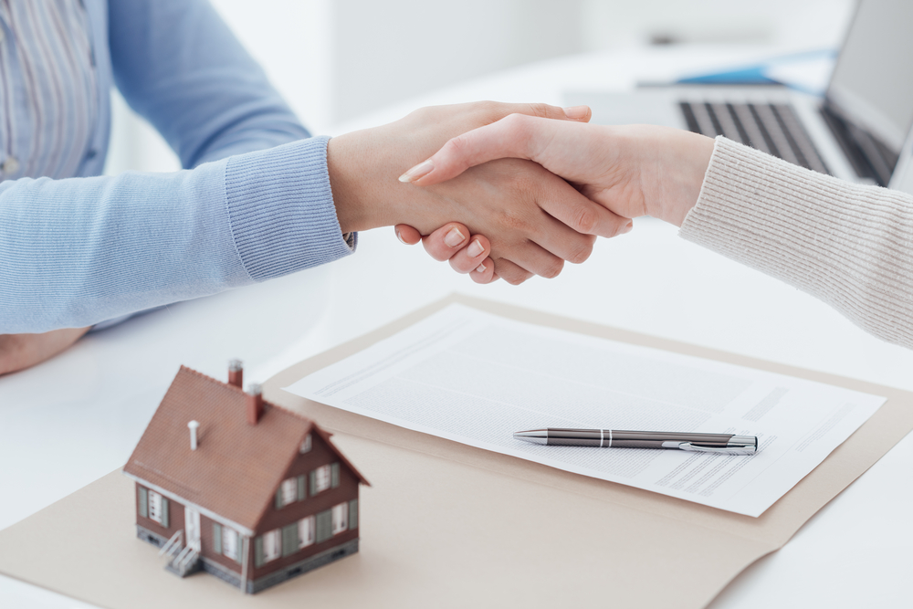 Shutterstock_ 580092196 Real estate broker and customer shaking hands after signing a contract: real estate, home loan and insurance concept
