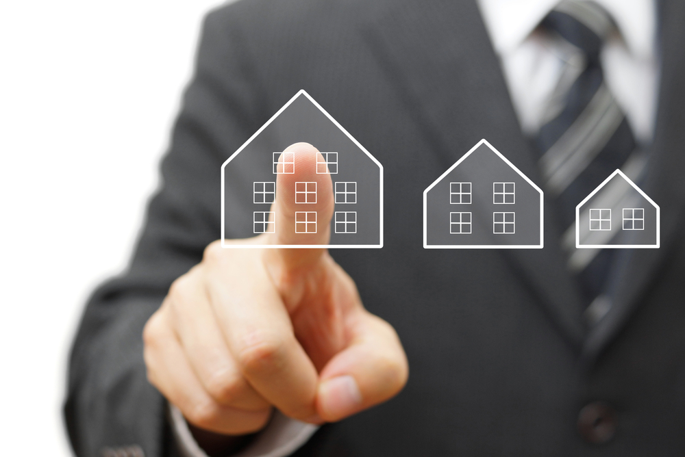 Shutterstock_210931240 Businessman touching virtual house. Mortgage,house savings or real estate concept