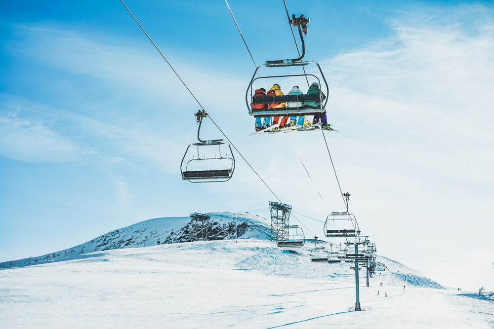 Shutterstock_ 1212119458 People on ski lift in winter ski resort - Holidays, snow gear renting, skiing, snowboarding and mountain landscape concept - Focus on guys sitting in cable car