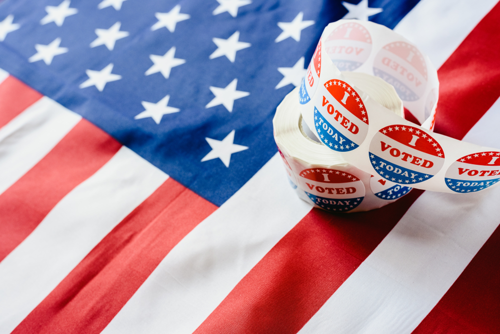 Shutterstock_1428892934 I vote today stickers roll, in US elections on American flag.