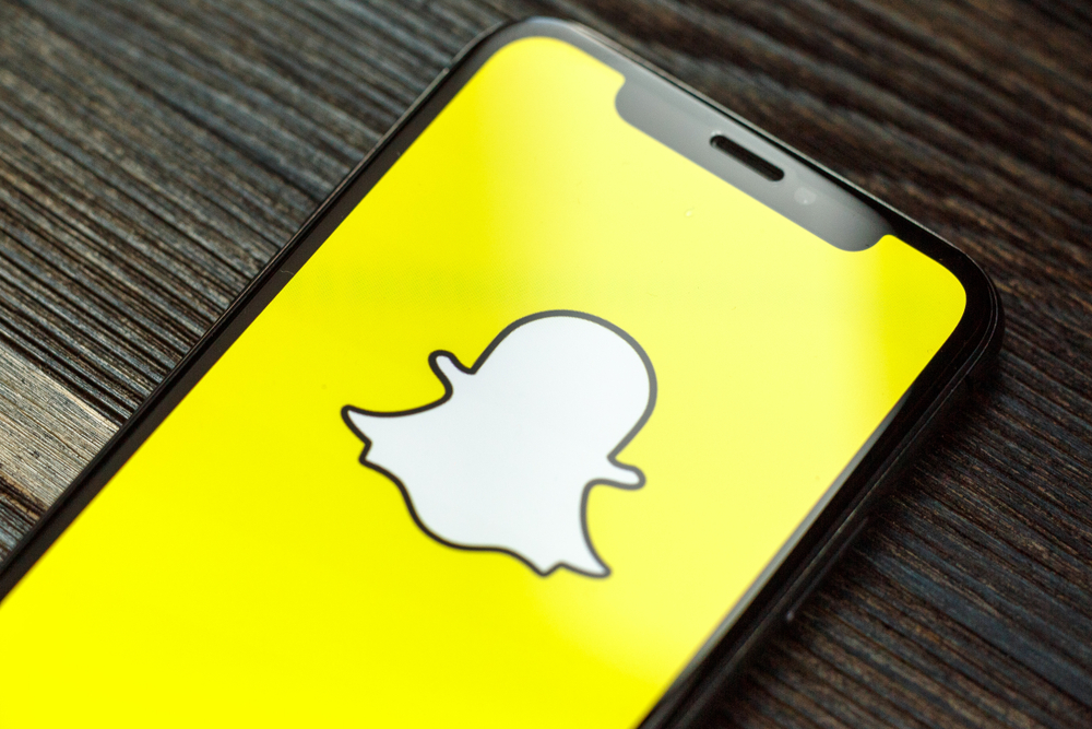 Shutterstock_1450562600 Snapchat logo on iPhone X screen. Snapchat is a social media app for smartphones.