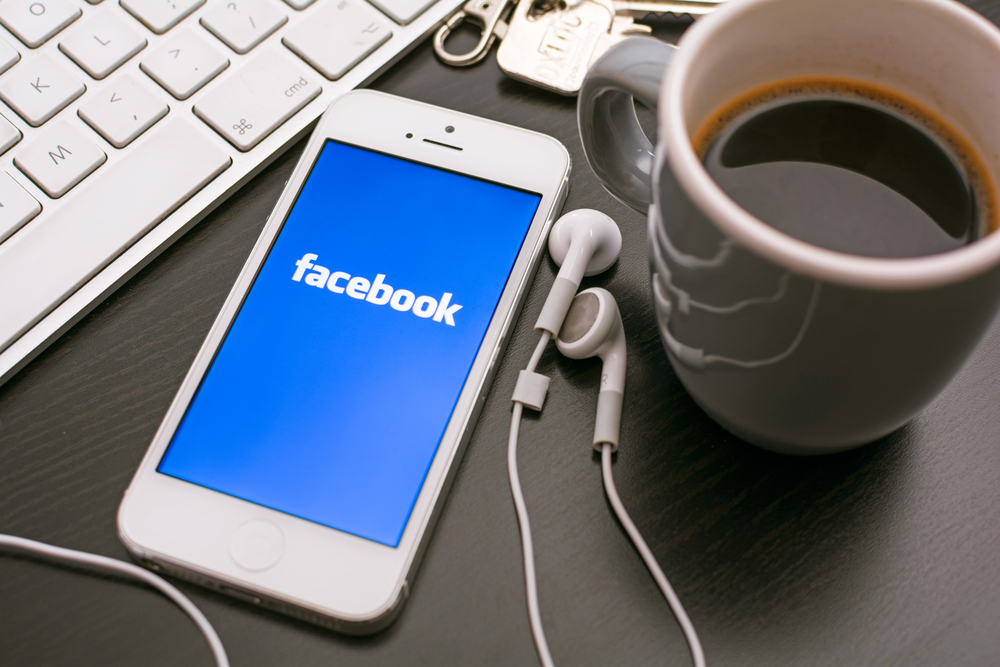 Shutterstock_170062403 Facebook app on mobile device laying on desk next to headphones, coffee cup and keyboard