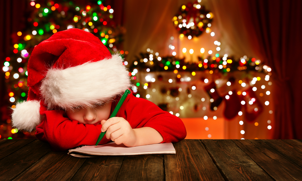 Shutterstock_331905611 Christmas Child Write Letter to Santa Claus, Kid in Santa Hat Writing Wish List, unfocused lights background