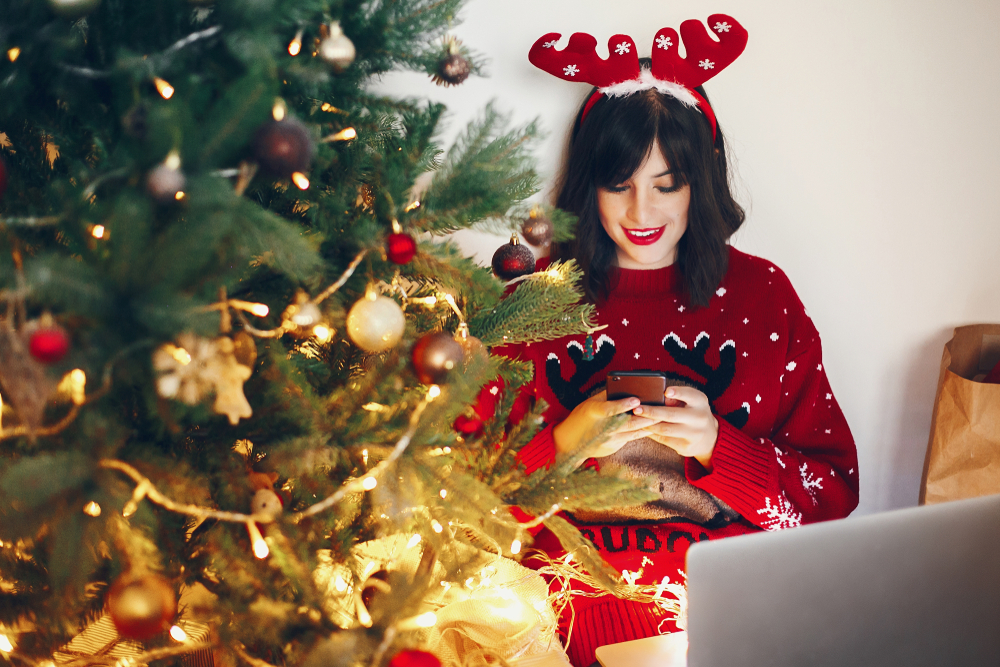 Shutterstock_ 775046200 Stylish woman in reindeer hat holding phone and laptop, under Christmas tree lights. shopping online, sale. space for text. seasonal greetings, happy holidays. social media