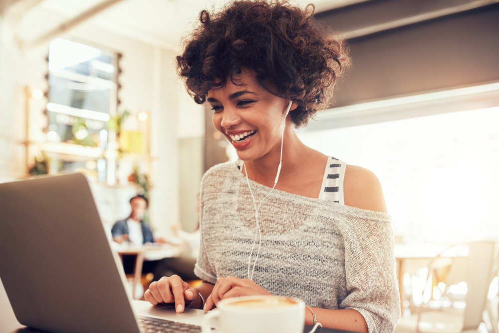 Shutterstock_409251190 Image of happy woman using laptop while sitting at cafe. Young african american woman sitting in a coffee shop and working on laptop