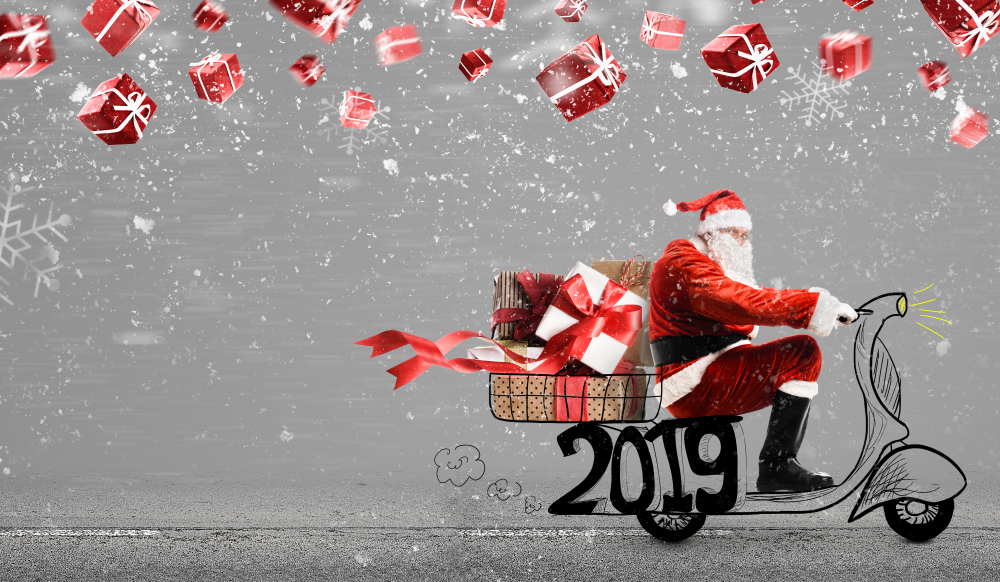 Shutterstock_1170478690 Santa Claus on scooter delivering Christmas or New Year 2019 gifts at snowy gray background