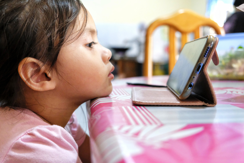 Shutterstock_1484572661 Young kids watching a video in smartphone gadget