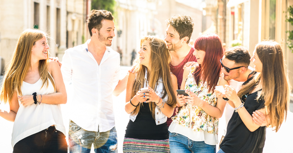 Shutterstock_1276934041 Best friends group having fun together on city street - Technology interaction concept in everyday lifestyle with millenials and gen z young people talking and using mobile smart phone