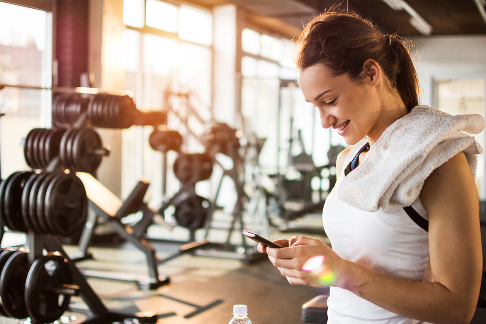 Shutterstock_397877713 Active girl with smartphone listening to music in gym.