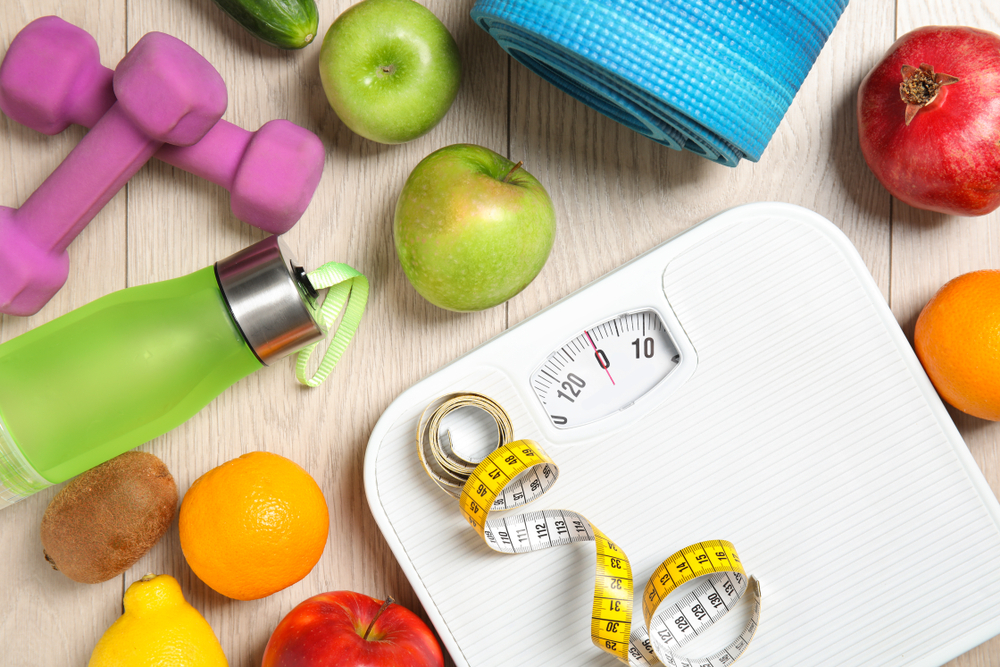 Shutterstock_1292487769 Flat lay composition with scales, healthy food and sport equipment on wooden background. Weight loss