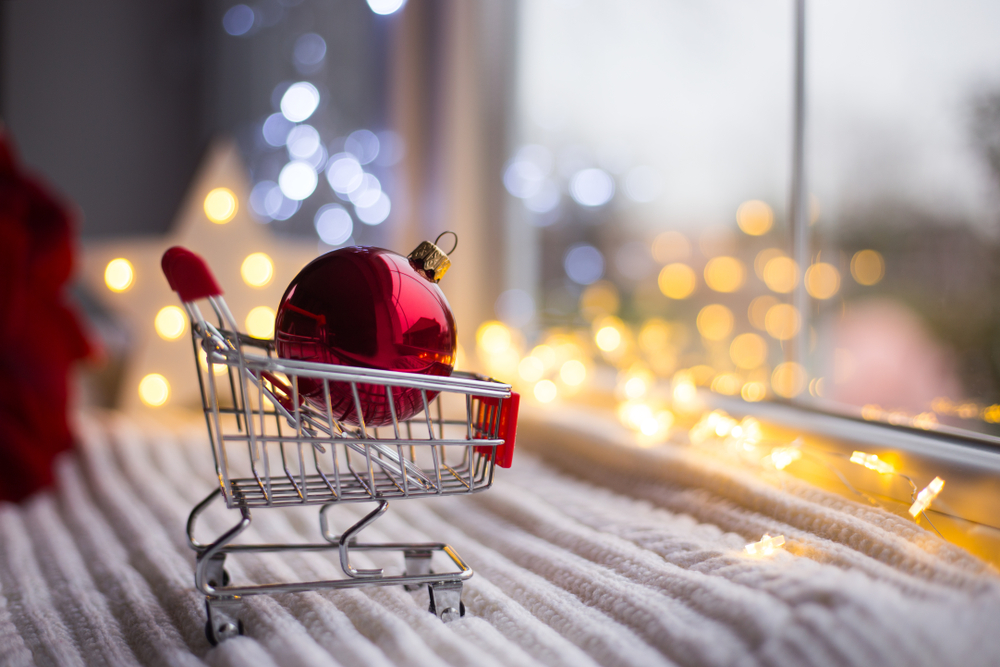 Shutterstock_1185684814 Red Christmas ball in toy supermarket trolley in daylight with warm garland bokeh on background. Festive magic lights. New Year shopping concept.