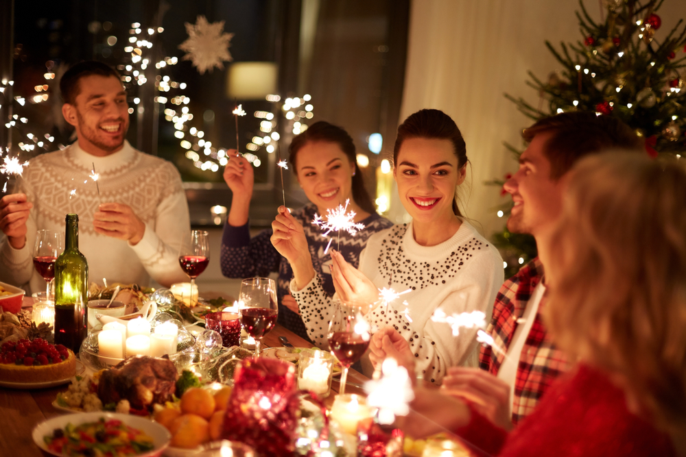 Shutterstock_1186831723 winter holidays and people concept - happy friends with sparklers celebrating christmas at home feast
