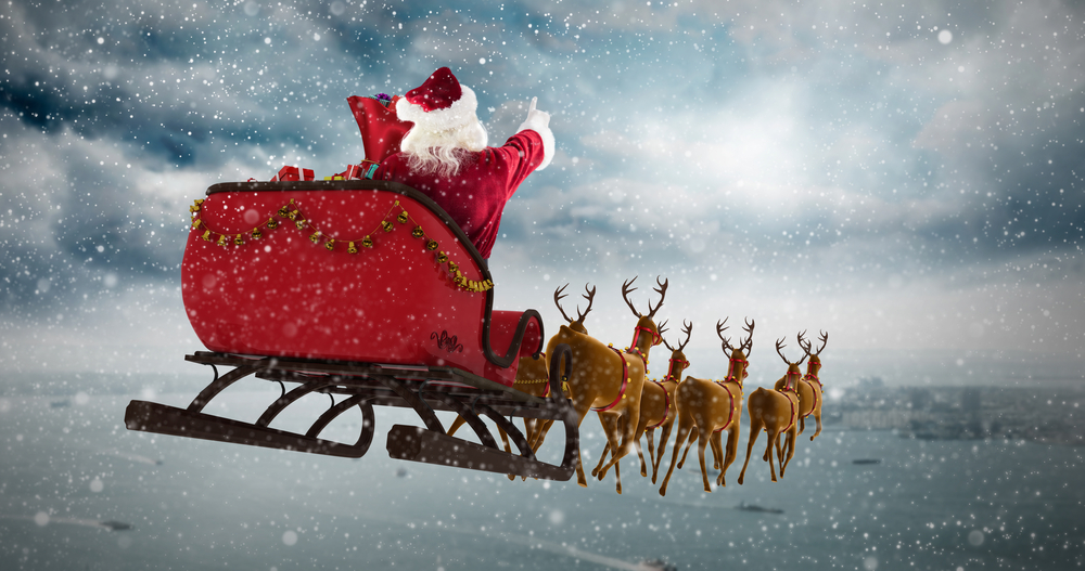 Shutterstock_513466336 Santa Claus riding on sleigh during Christmas against coastline and city