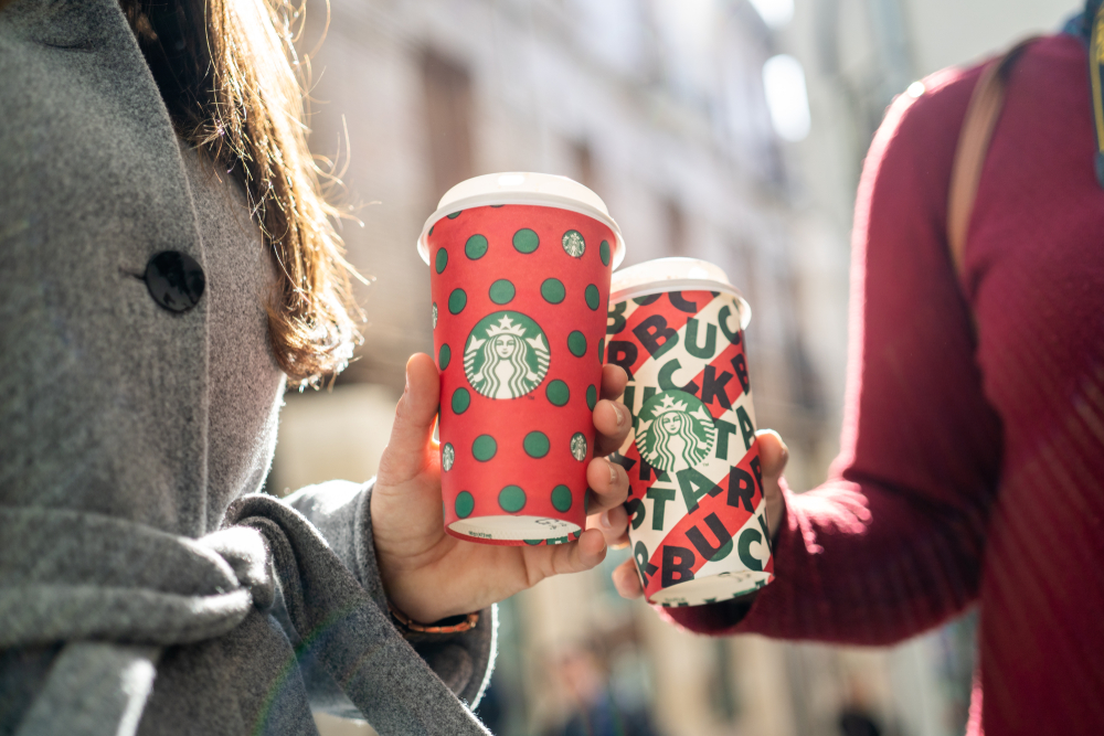 Shutterstock_ 1583256532 Close up of a Two Young Business Woman Holding tall Christmas Starbucks Coffee on the street during sunset in New york. Starbucks is the world's largest coffee house