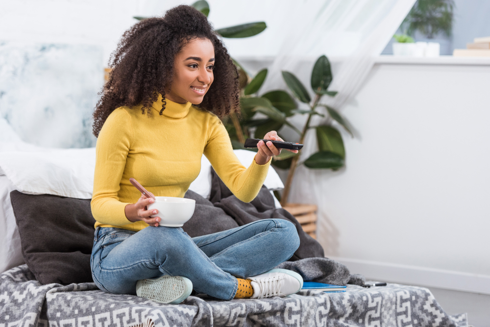 Shutterstock_ 1256409751 attractive stylish african american girl holding bowl with food and watching tv at home