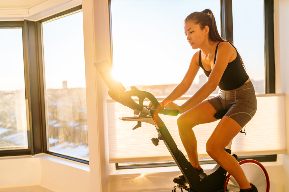 Shutterstock_1291114891 Home fitness workout woman training on smart stationary bike indoors watching screen connected online to live streaming subscription service for biking exercise. Young Asian woman athlete.