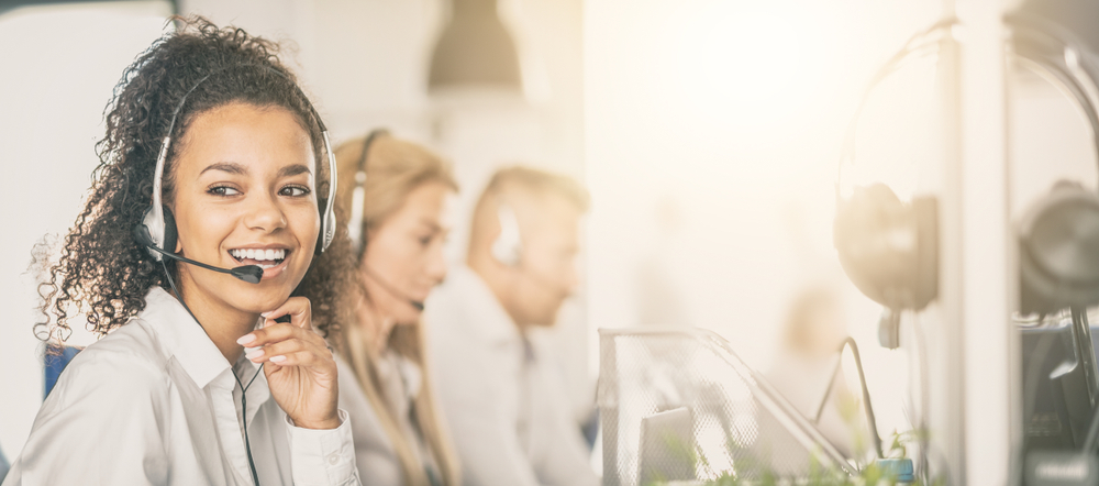 Shutterstock_1232587621  Call center worker accompanied by her team. Smiling customer support operator at work. Young employee working with a headset.