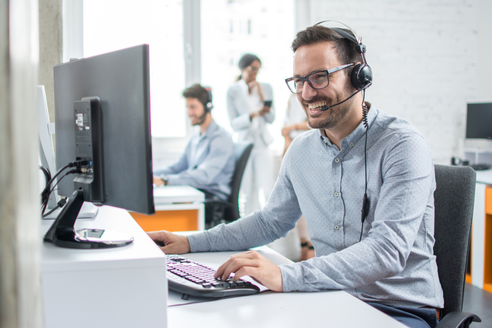 Shutterstock_1035280786  Smiling customer support operator with hands-free headset working in the office.