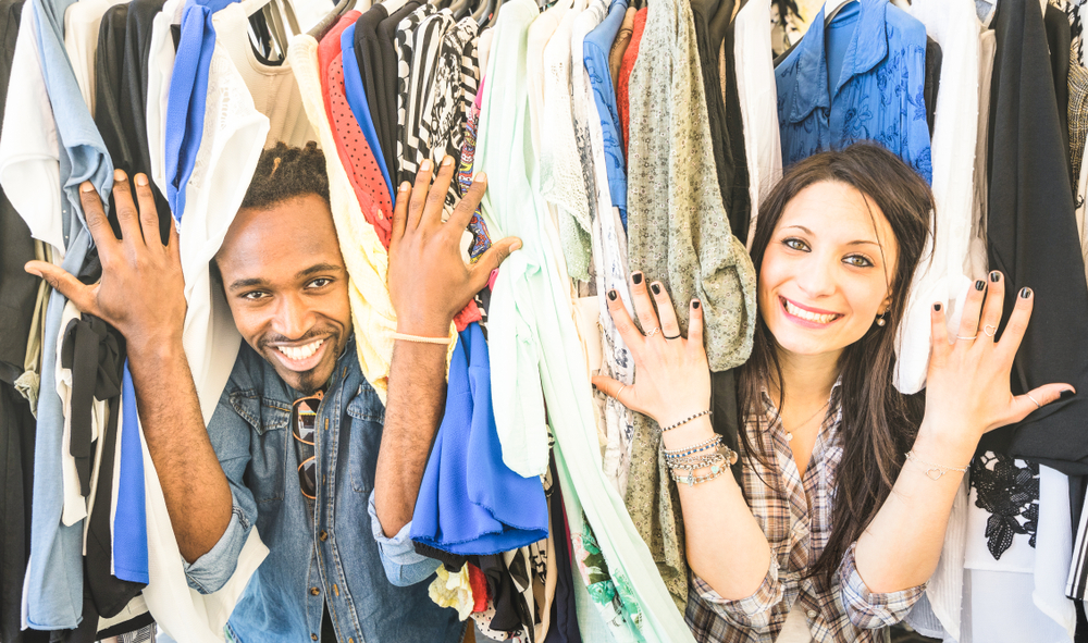 Shutterstock_1017455884 Young multiracial couple having fun at clothing flea market - Best friends sharing time shopping on cheap sale - Lovers enjoying everyday life moments - Wardrobe fashion shop concept with happy people