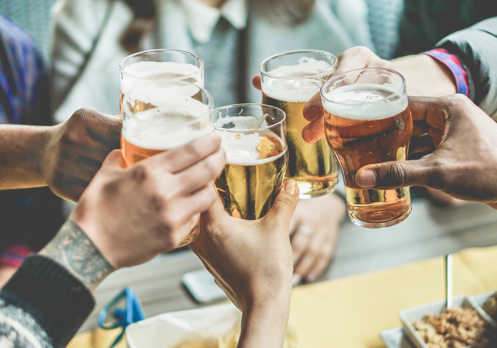 Shutterstock_507392950 Multiracial group of friends enjoying a beer - Young people hands toasting and cheering aperitif beers half pint - Friendship and youth concept - Warm vintage raw filter - Focus on bottom hand