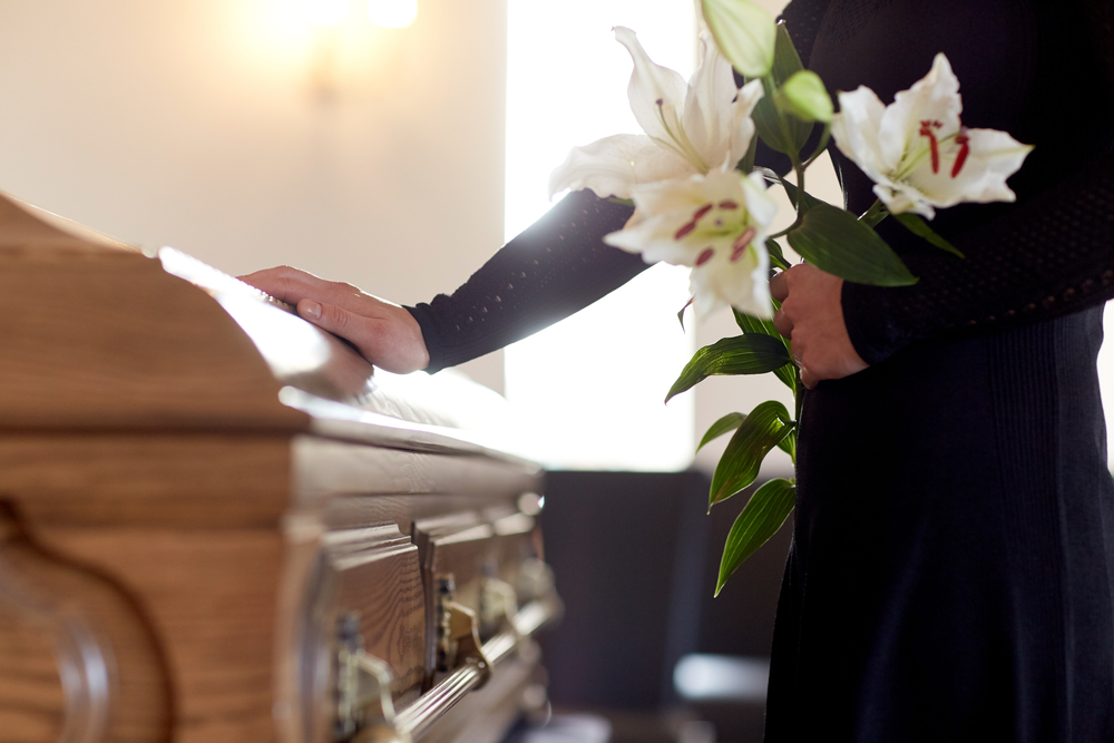 Shutterstock_664197991 people and mourning concept - woman with white lily flowers and coffin at funeral in church