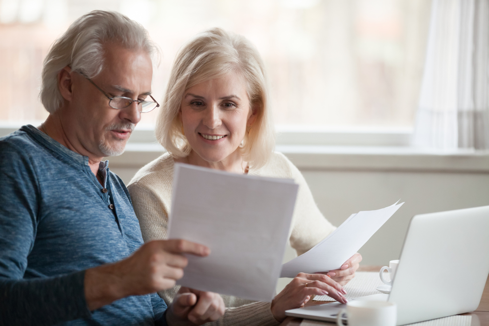 Shutterstock_1185179278 Happy old middle aged couple holding reading good news in document, smiling senior mature family excited by mail letter, checking paying domestic bills online on laptop, discussing budget planning