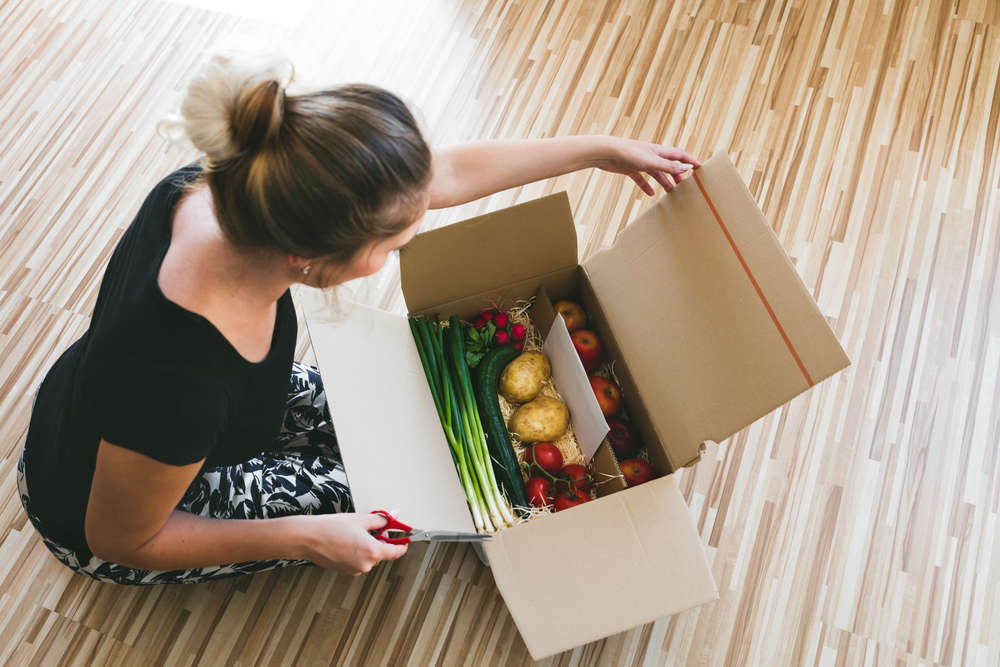 Shutterstock_491848777 woman opening a vegetable delivery box at home, online ordering