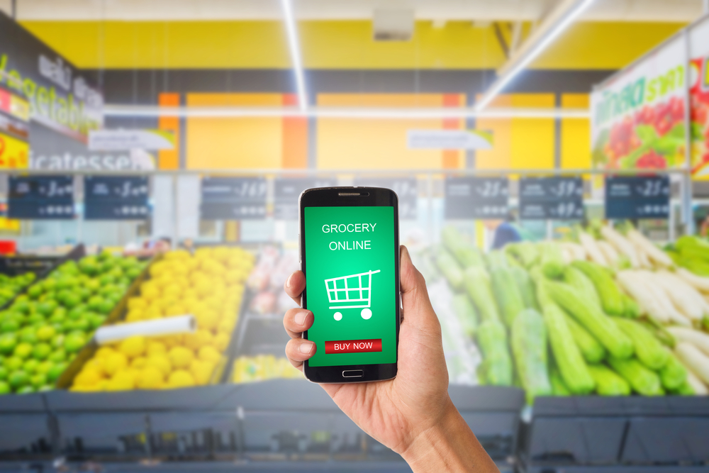 Shutterstock_555054529 Hand holding mobile with grocery online on screen with blur supermarket background