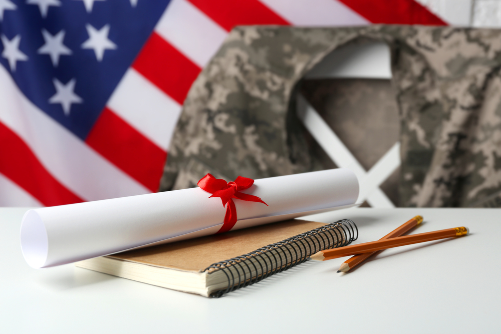 Shutterstock_555572494 Notebook, diploma and pencils on white table. USA military education concept