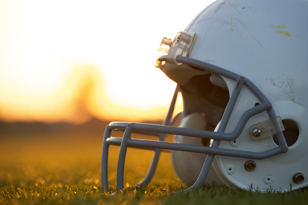 Shutterstock_149768081 American Football Helmet on the Field at Sunset with room for copy