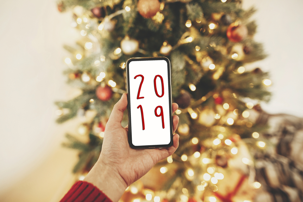 Shutterstock_1236800011 2019 text on phone screen on background of golden beautiful christmas tree with lights in festive room. Season's greetings card. Merry Christmas and Happy New Year