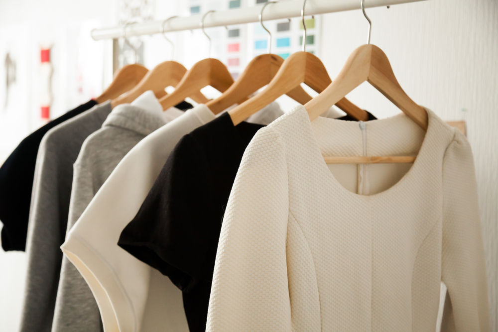 Shutterstock_1006128949 Women dresses new collection of stylish clothes wear hanging on hangers clothing rack rails, fabric samples at background, fashion design studio store concept, dressmaking tailoring sewing workshop