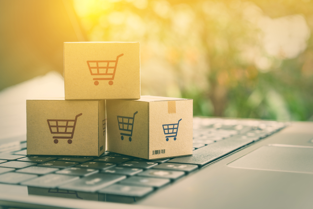 Shutterstock_1025051812 Online shopping / ecommerce and delivery service concept : Paper cartons with a shopping cart or trolley logo on a laptop keyboard, depicts customers order things from retailer sites via the internet.