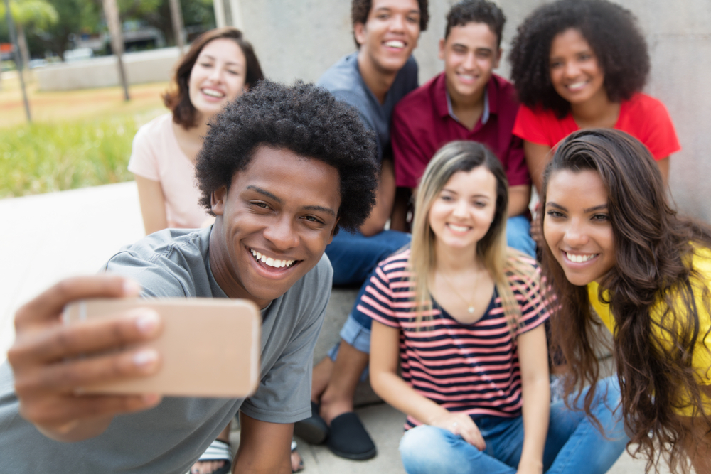 Shutterstock_765053950 Large group of international young adults taking selfie with phone outdoor in the summer